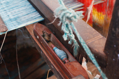 A close up of a loom with a shuttle and blue coloured yarn