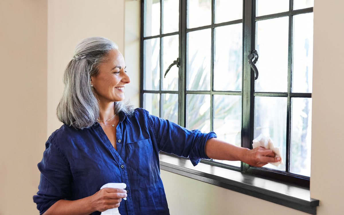 Woman happily cleaning her house window from the inside with Glass Cleaner
