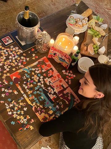 Woman drinking wine whilst doing a cool jigsaw puzzle