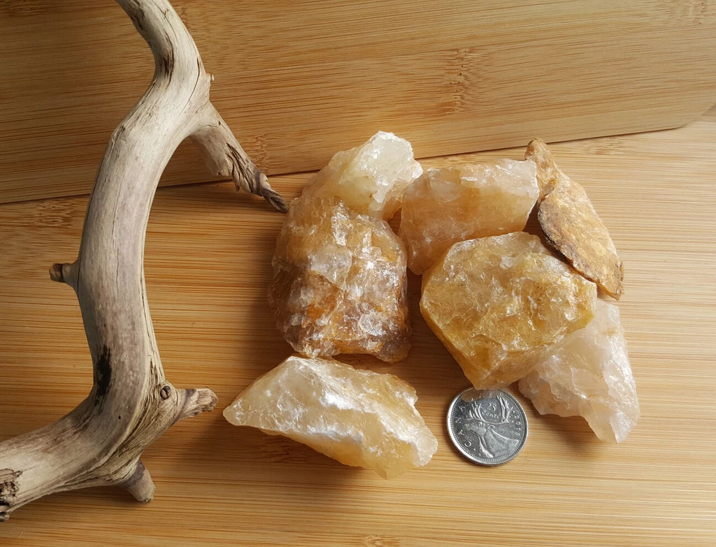 raw unpolished yellow crystal beside woody branch placed on a wooden surface