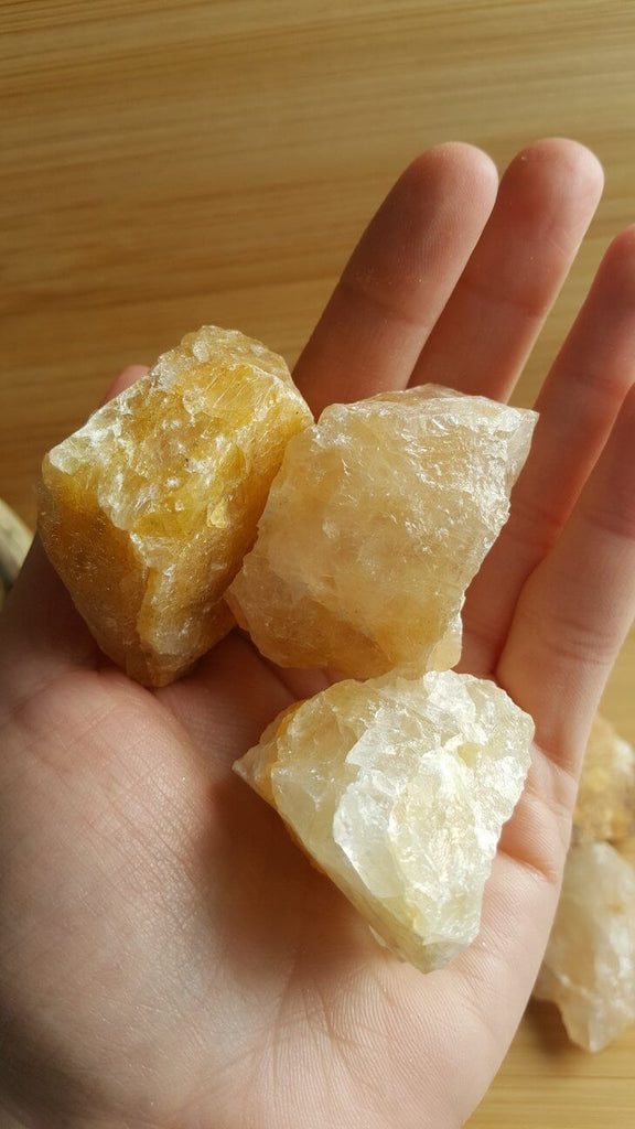 hand holding three pieces yellow unpolished crystal rocks