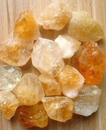 pieces of raw citrine stones placed on a wooden surface top flat lay view