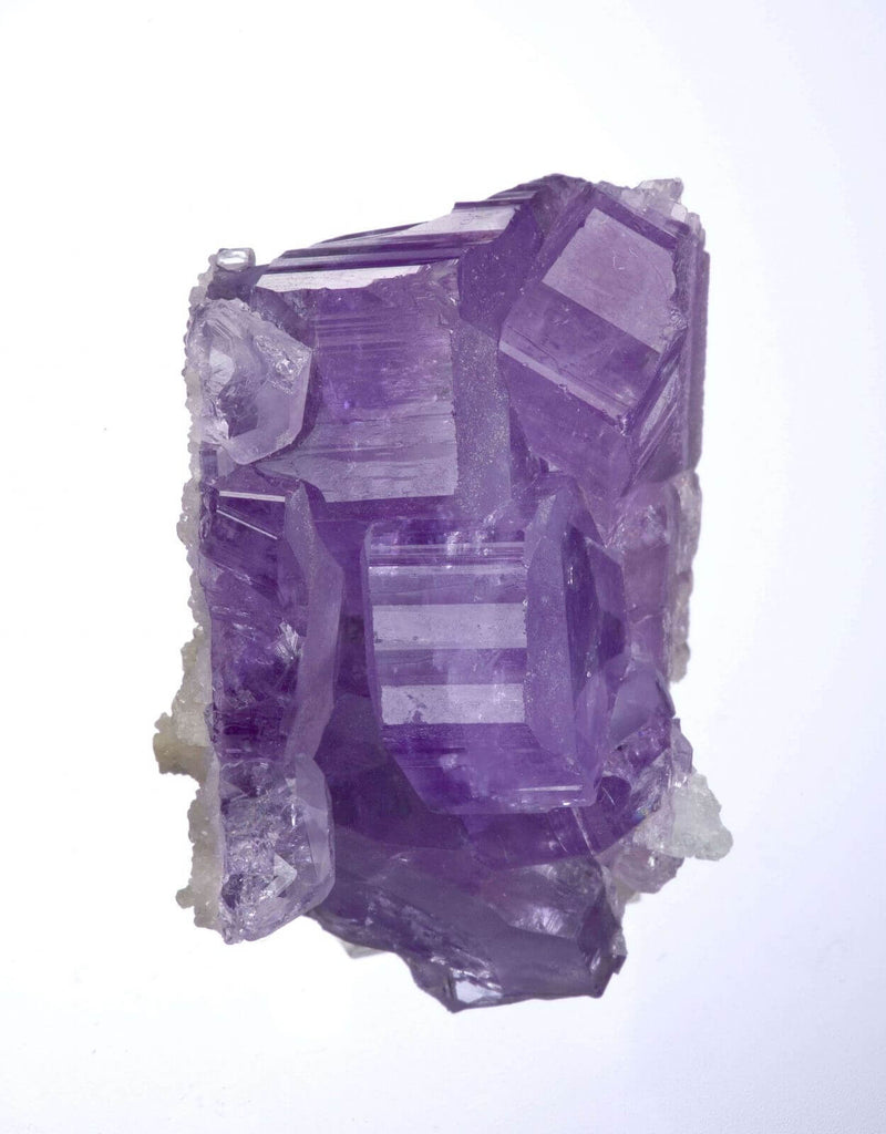 purple cut crystal rock white lining close up view white background