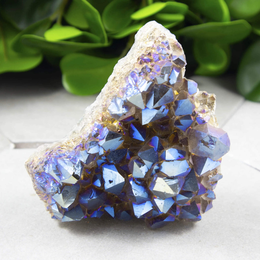 raw blue amethyst placed on a white surface with leaves background