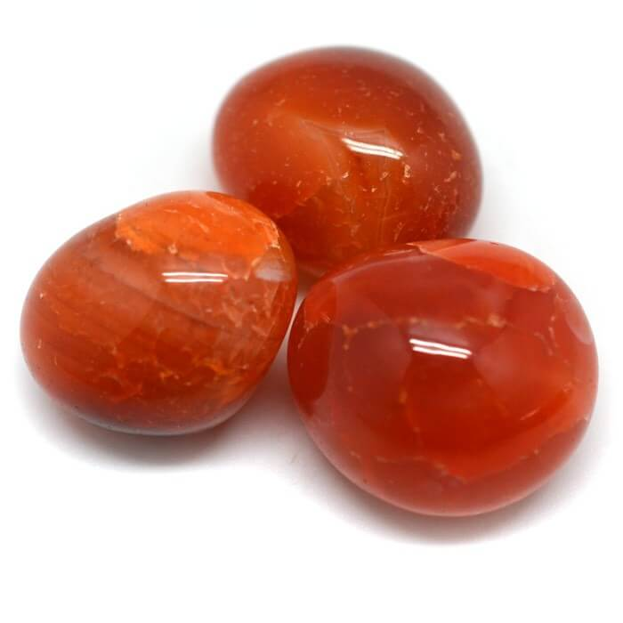 three pieces of orange smooth stone white background close up view