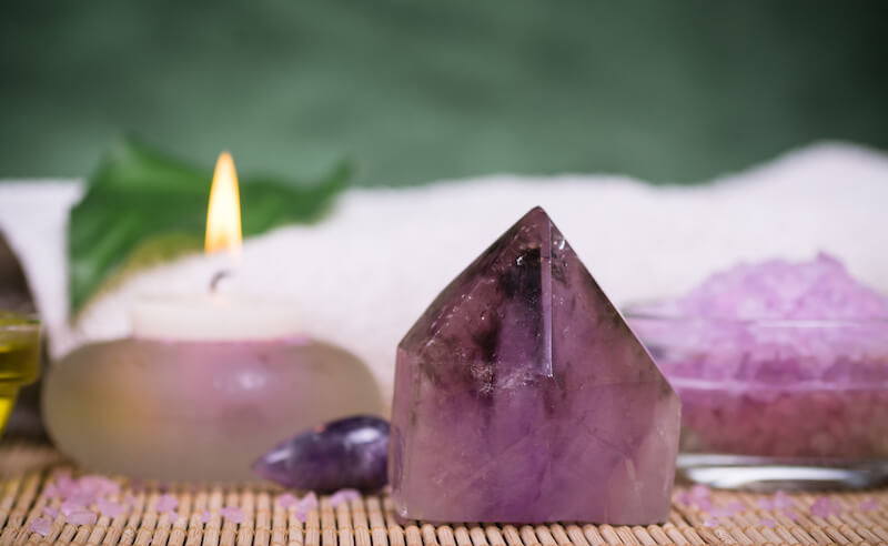 purple crystals and candle placed on a wooden mat