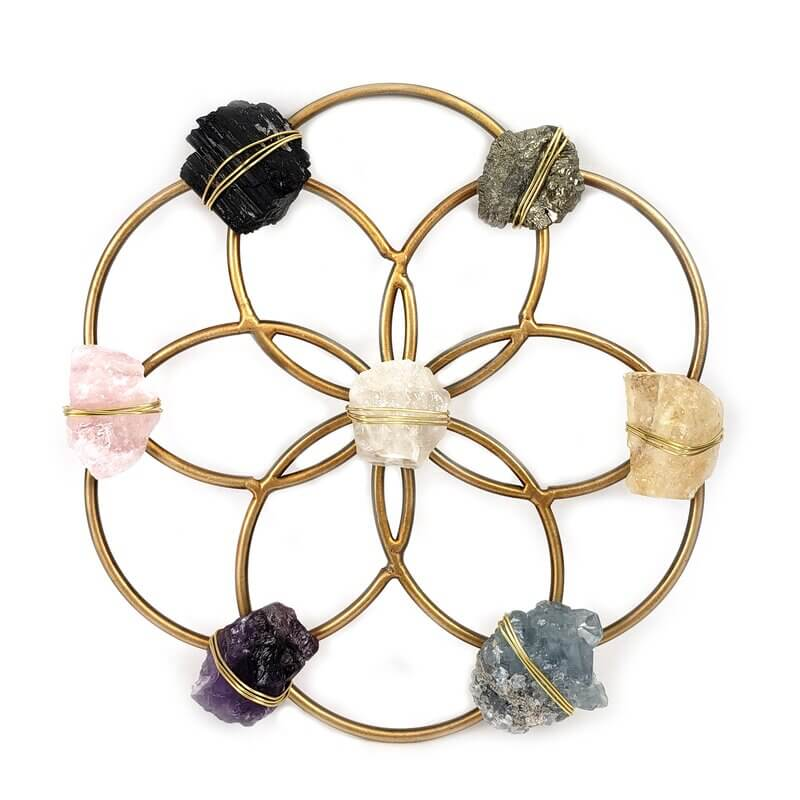 different types colors of raw crystal rocks tied to a gold crystal grid