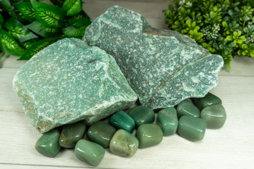 large pieces of green unpolished rock beside many pieces of square shaped smooth green stones