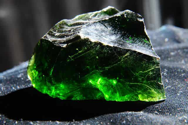 green cut crystal rock on a gray cloth background