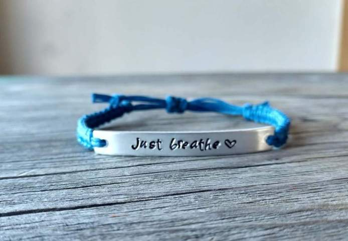 blue tied bracelet with a metal engraving just breathe