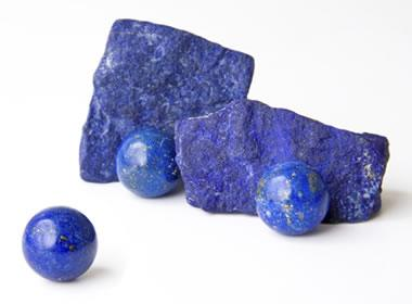 three pieces of smooth circle gem stones beside two raw blue crystal rocks