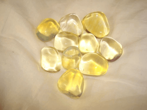 pieces of smooth yellow gem stones brown cloth background