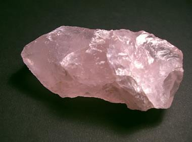 pink raw crystal rock placed on a dark surface close up view