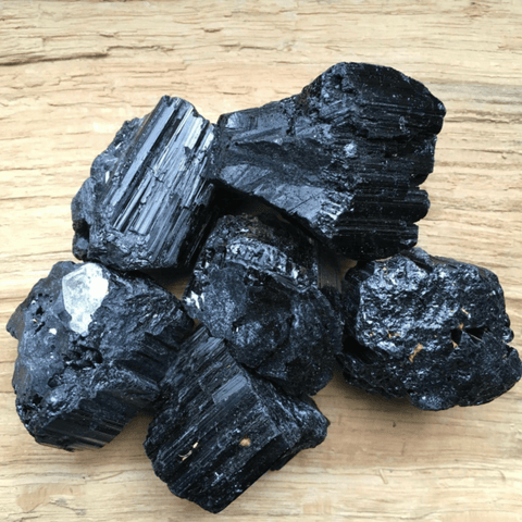 six pieces of raw unpolished black tourmaline placed on a yellow surface close up view