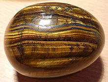 piece of tiger eye smooth stone yellow and black horizontal linear pattern
