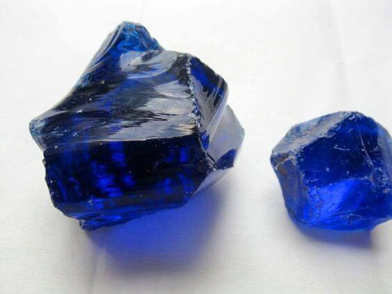 two pieces of blue crystal rock close up view white background
