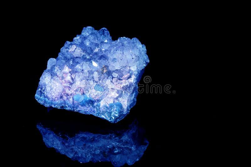 blue unpolished crystal on a black background close up view