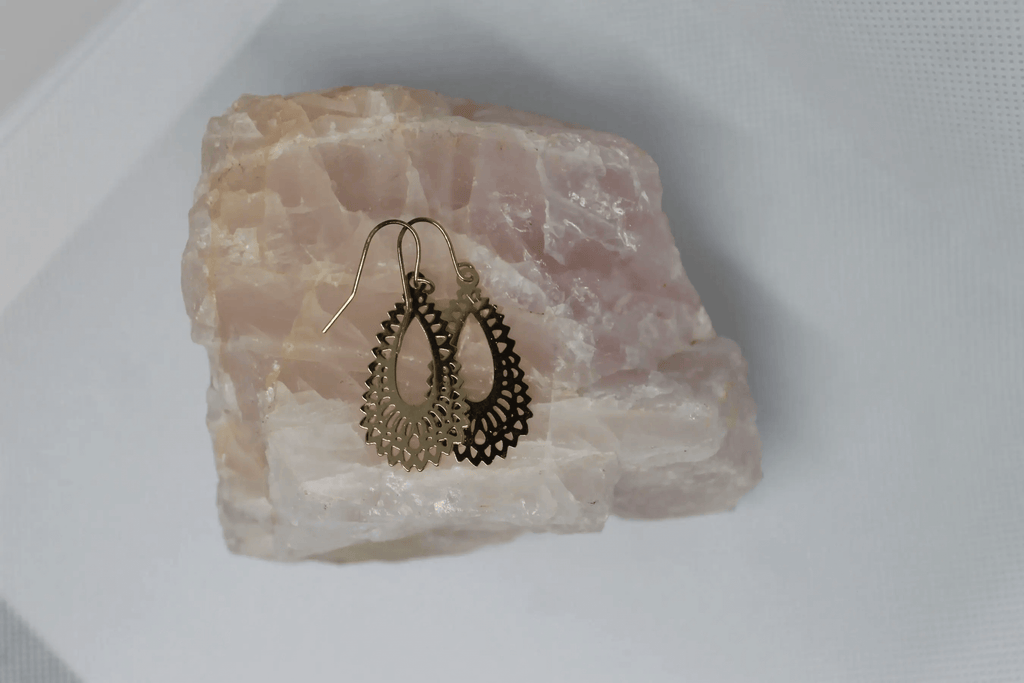 pair dangling earrings placed on top of a pink unpolished crystal rock