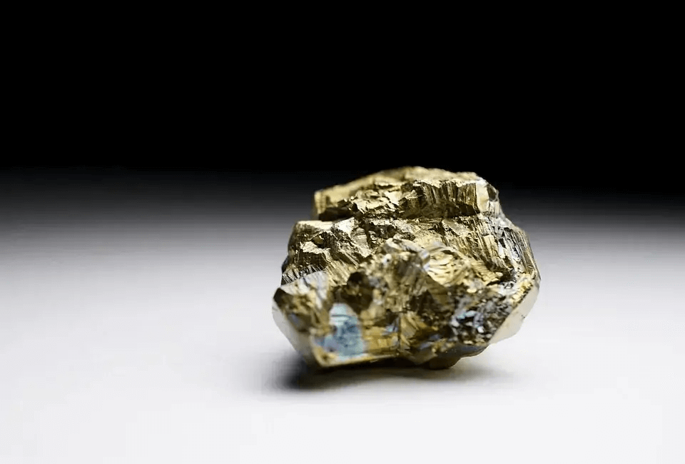 small pyrite rock gold color on a black and white background