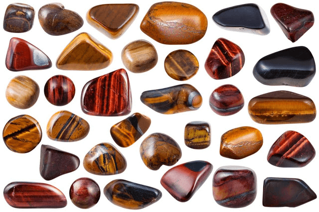 different types sizes shapes of smooth stones neatly arranged white background