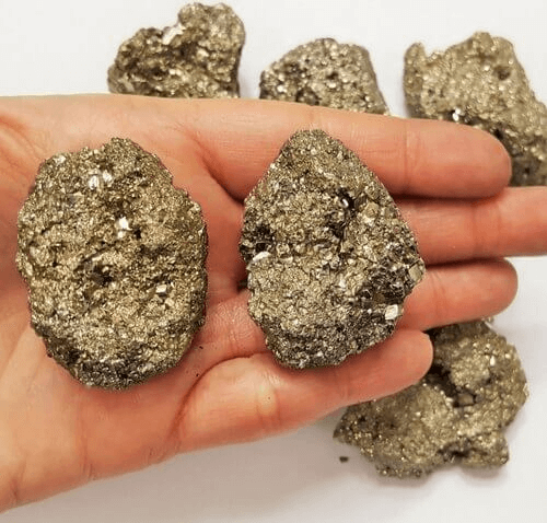 two small pyrite rocks placed on a palm
