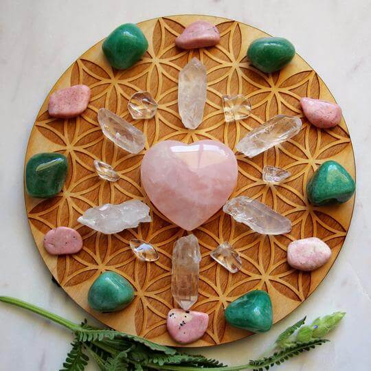 pink green white clear crystal rock and smooth gem stones arranged on a circle woodensurface