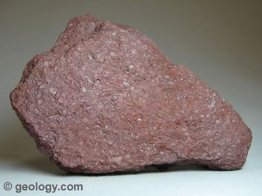 unpolished red rock close up view white background