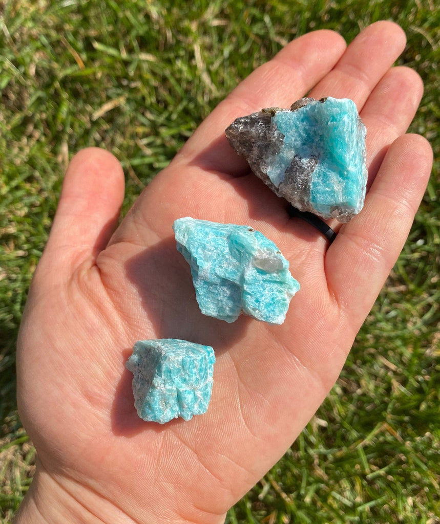 three pieces of different sized raw turquoise rock placed on a hand