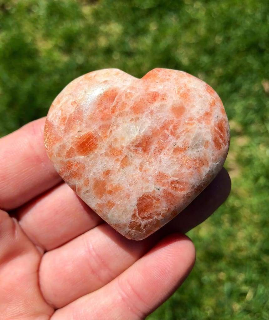 heart shaped orange stone placed on a hand's fingertips