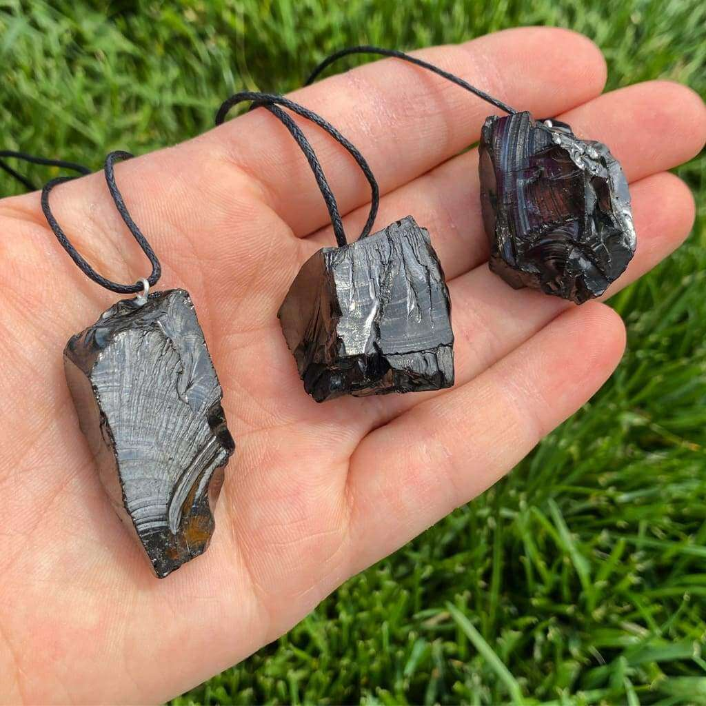 hand holding three necklaces with black crystal rock pendants