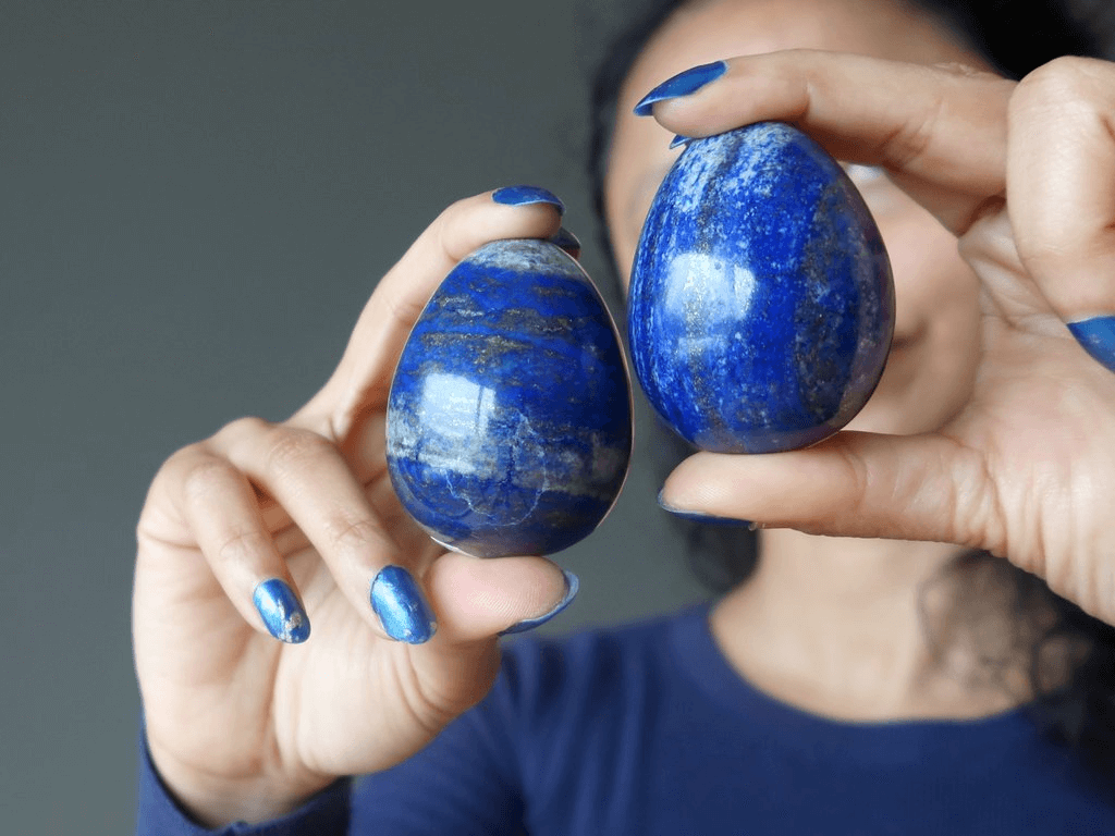 woman wearing blue and blue nail polish holding two egg shaped blue smooth stones