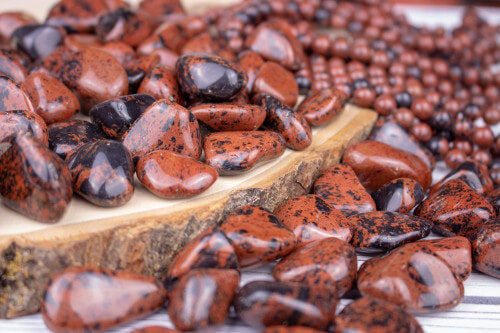 many pieces of smooth brown stones with black spots on wooden surface and white background