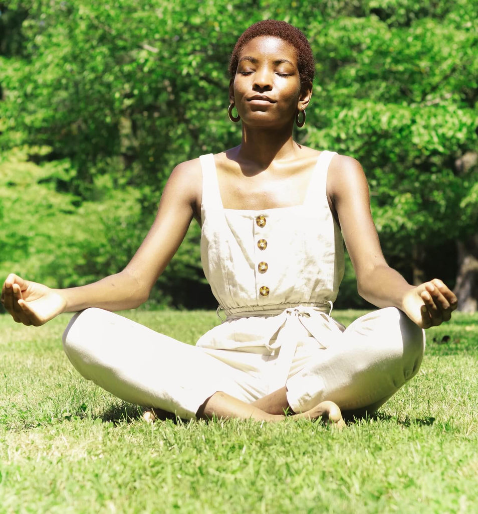 African woman wearing white jumpsuit sitting in a lotus yoga position