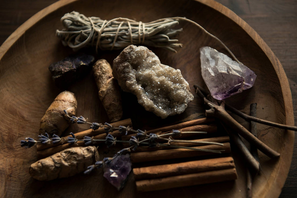 different types of crystal rocks herbs sticks placed on a wooden plate