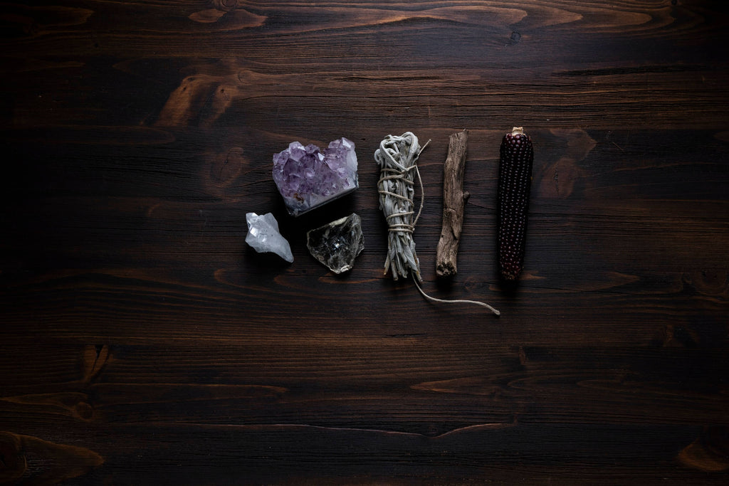 different types of crystal rocks beside smudging sages on a dark wooden surface