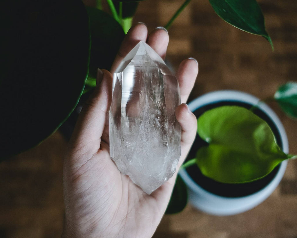 hand holding large clear crystal prism cup of liquid and leaf beside