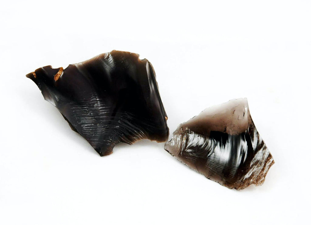 two pieces of dark brown black crystal rock white background