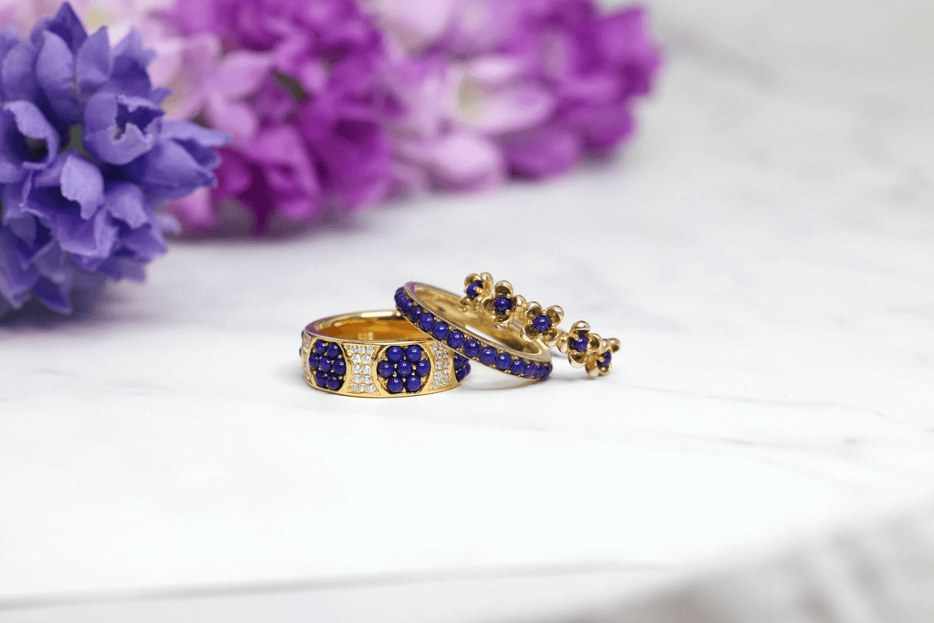 three gold ring encrusted with blue stones placed on a white cloth surface