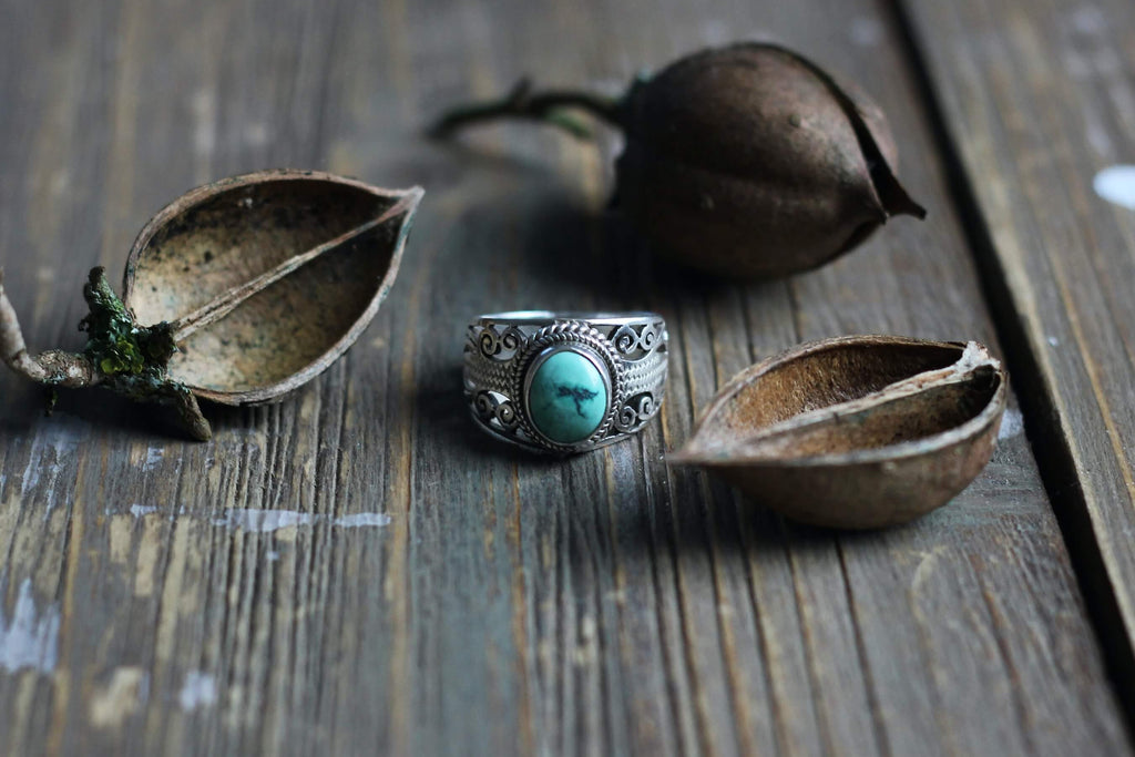 silver ring with circle smooth turquoise stone placed on a wooden surface