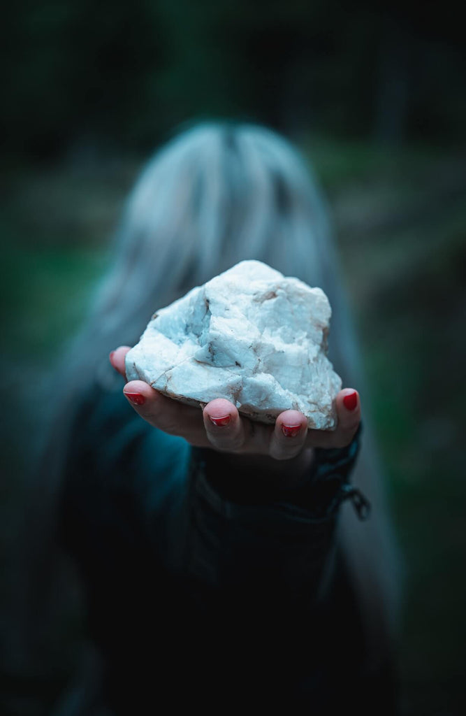 hand holding white unpolished rock selective focus