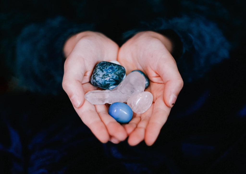hands holding blue and white smooth stones and crystals black background
