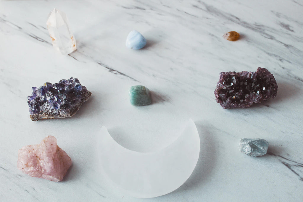 different pieces of rocks and crystals with different colors placed on a white marble surface