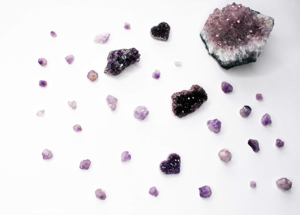 pieces of purple crystal rocks different sizes and shapes scattered on a white background