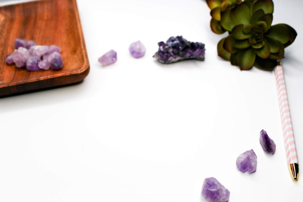 tiny pieces of purple crystal rocks on a wooden plate some scattered on a white background