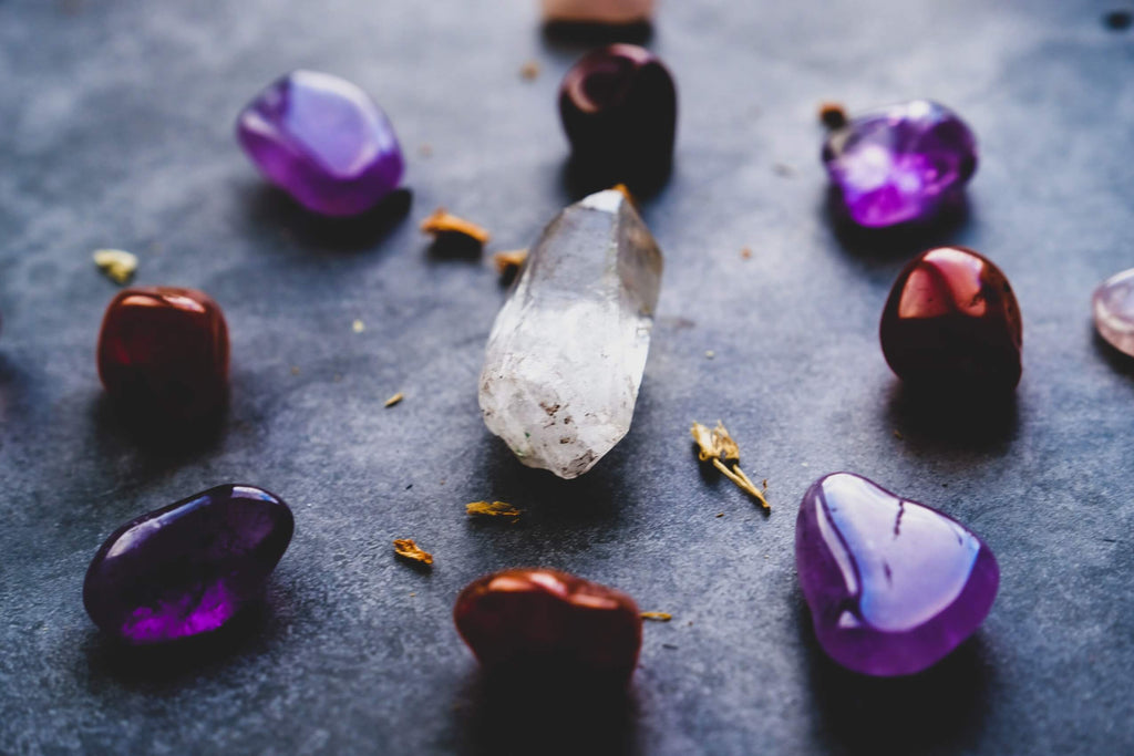 purple and red smooth stones arranged in a circle with a clear crystal in the center