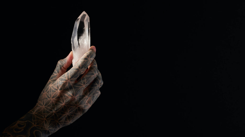 tattooed hand holding white clear crystal black background