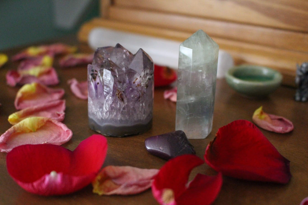 purple and greenish crystals surrounded by rose petals