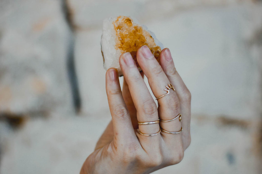 hand wearing many thing gold rings holding white yellow crystal geode