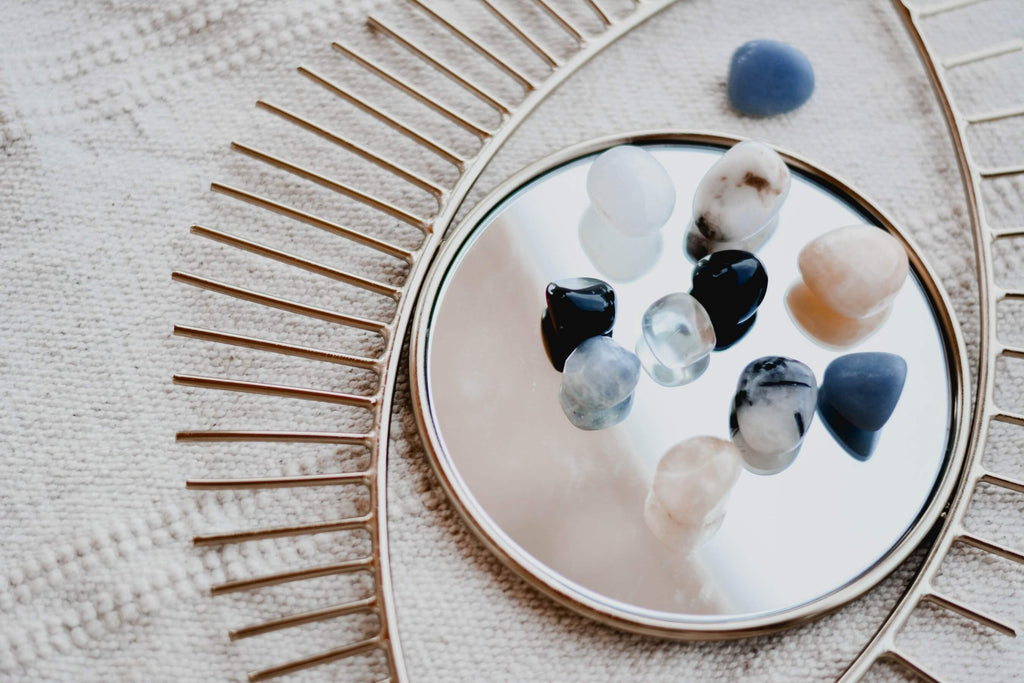 different types colors of smooth gems stones and crystal rocks placed on a mirror