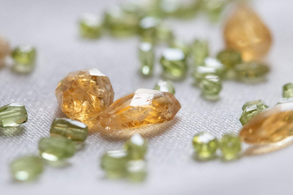 tiny yellow and green gem and beads placed on a cloth surface